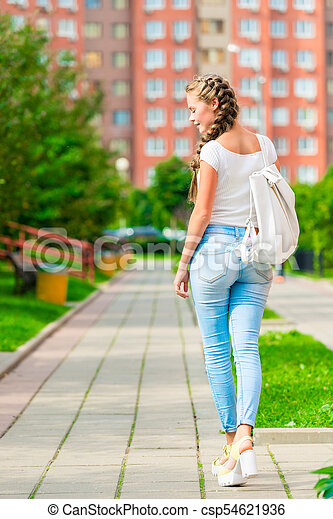 beautiful young woman walks around city with backpack, rear view - csp54621936