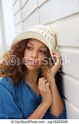 Beautiful young woman wearing hat and leaning against wall - csp16223548