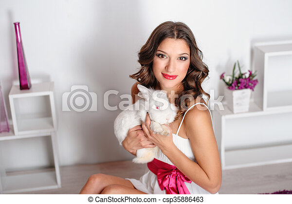 Beautiful young woman with a pet rabbit in studio - csp35886463