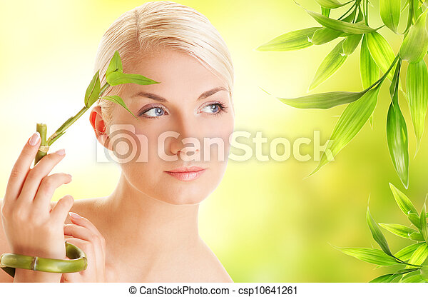Beautiful young woman with bamboo plant - csp10641261