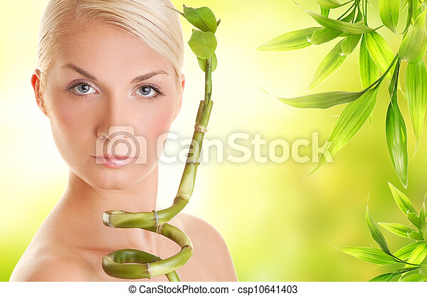 Beautiful young woman with bamboo plant - csp10641403