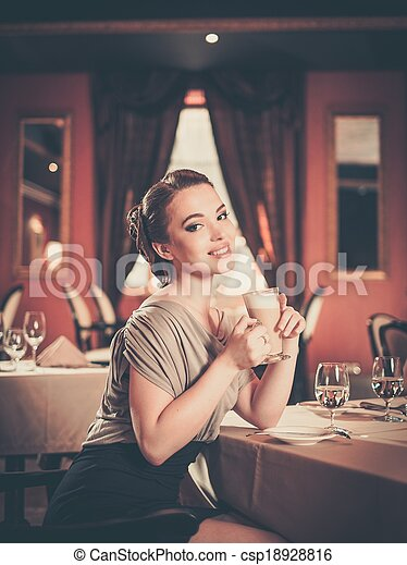 Beautiful young woman with cup of coffee alone in a restaurant - csp18928816