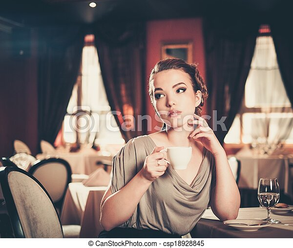 Beautiful young woman with cup of coffee alone in a restaurant - csp18928845