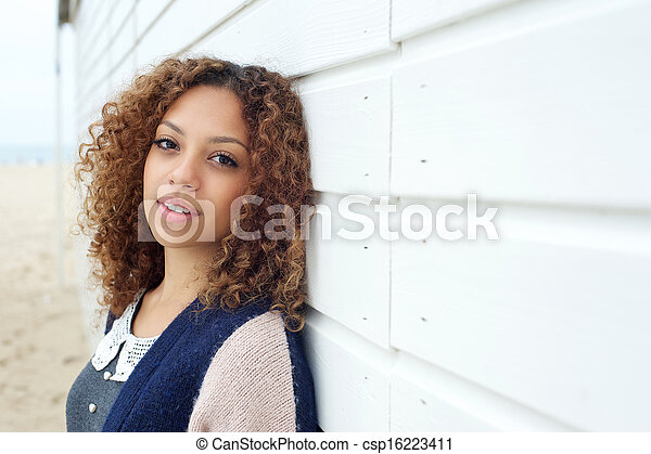 Beautiful young woman with curly hair posing outdoors - csp16223411