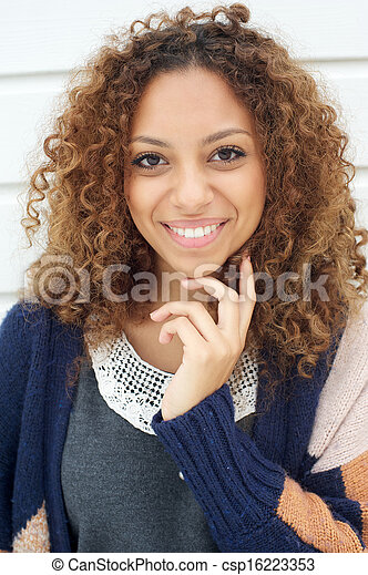 Beautiful young woman with curly hair smiling outdoors - csp16223353