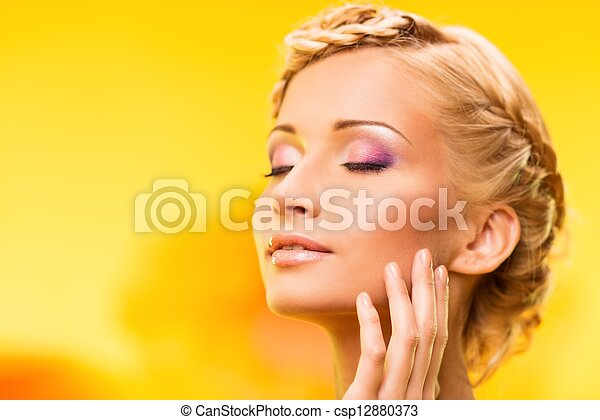 Beautiful young woman with hairdo touching her face with hand - csp12880373