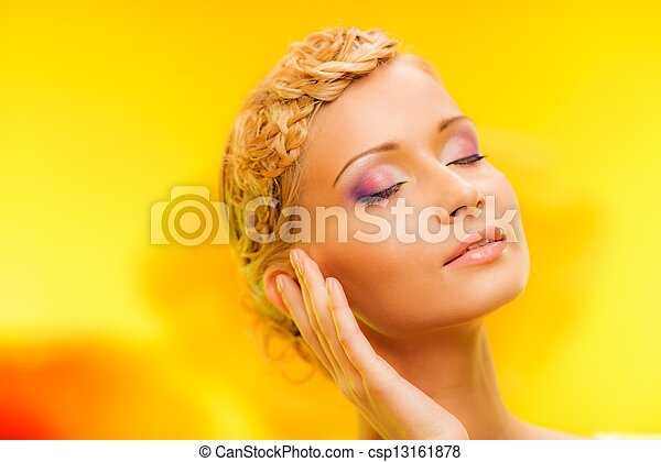 Beautiful young woman with hairdo touching her face with hand - csp13161878