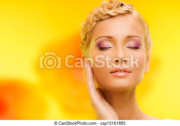 Beautiful young woman with hairdo touching her face with hand - csp13161883