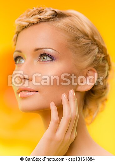 Beautiful young woman with hairdo touching her face with hand - csp13161884