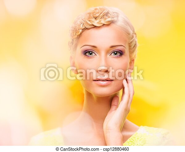 Beautiful young woman with hairdo touching her face with hand - csp12880460