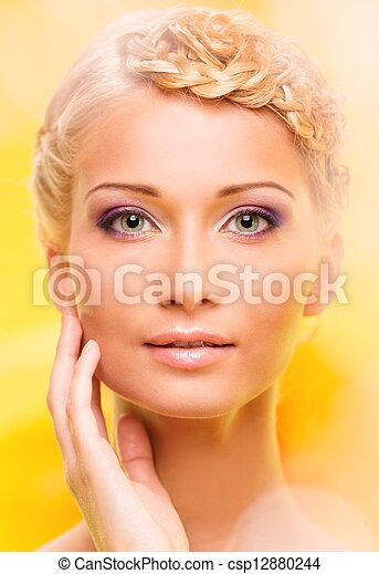 Beautiful young woman with hairdo touching her face with hand - csp12880244