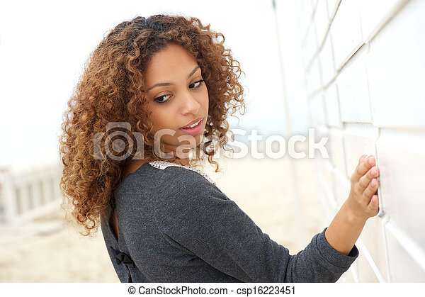 Beautiful young woman with hand on wall and looking over shoulder - csp16223451