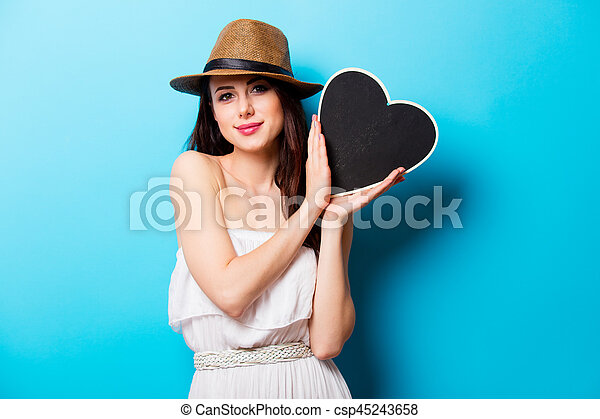 beautiful young woman with heart shaped toy standing in front of wonderful blue background - csp45243658
