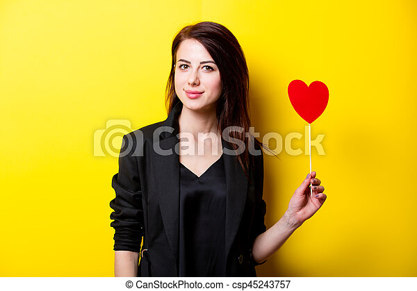 beautiful young woman with heart shaped toy standing in front of wonderful yellow background - csp45243757
