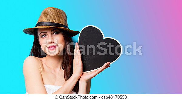 beautiful young woman with heart shaped toy standing in front of wonderful blue background - csp48170550