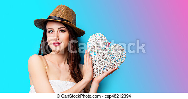 beautiful young woman with heart shaped toy standing in front of wonderful blue background - csp48212394