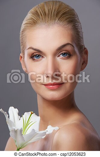 Beautiful young woman with lily flower - csp12053623