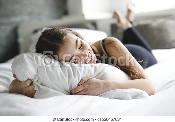 beautiful young woman with long hair sleeping on bed in bedroom - csp50457031