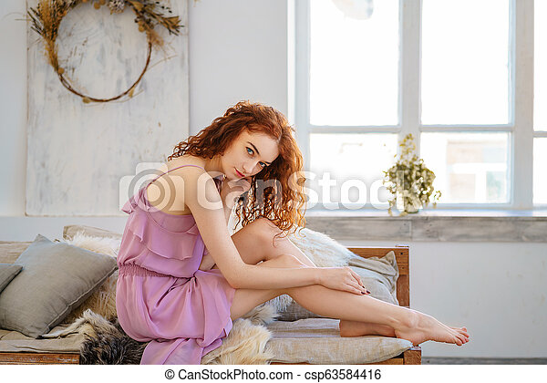 beautiful young woman with red hair sitting sad - csp63584416