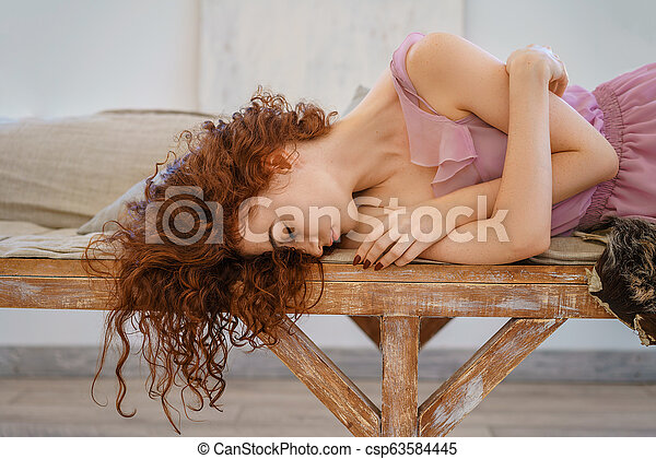 beautiful young woman with red hair sitting sad - csp63584445
