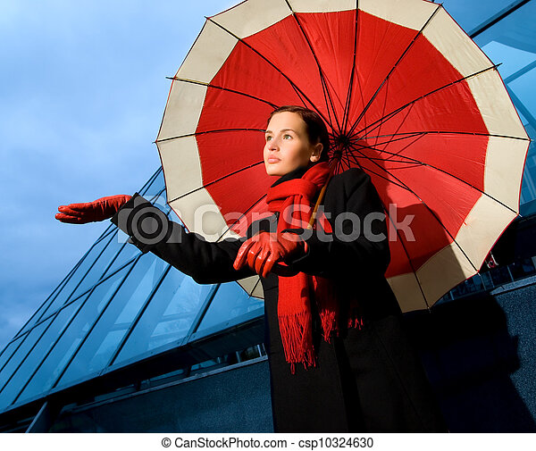 Beautiful young woman with red umbrella on rainy day - csp10324630