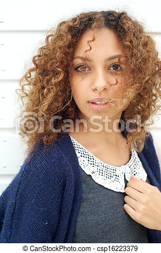 Beautiful young woman with wind blowing hair across face - csp16223379