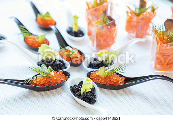 Beautifully decorated catering banquet table with different food salad, caviar on corporate christmas birthday party event or wedding celebration - csp54148621