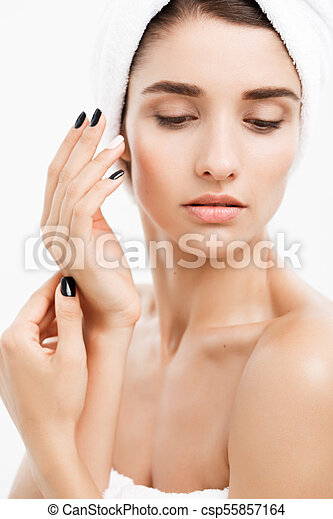 Beauty and Skin care concept - Close up Beautiful Young Woman touching her skin - csp55857164