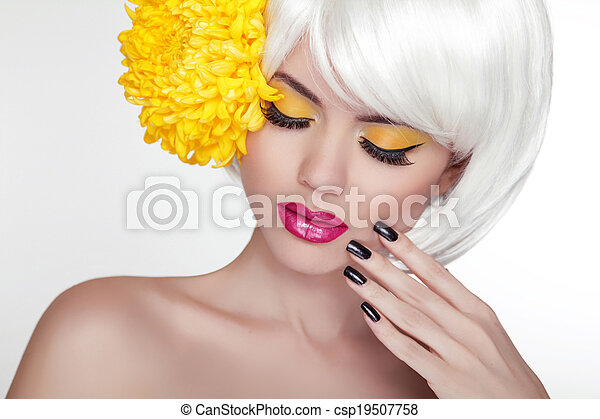 Beauty Blond Female Portrait with yellow flower. Beautiful Spa Woman Touching her Face. Makeup and manicured nails. Perfect Fresh Skin. Isolated on white background - csp19507758