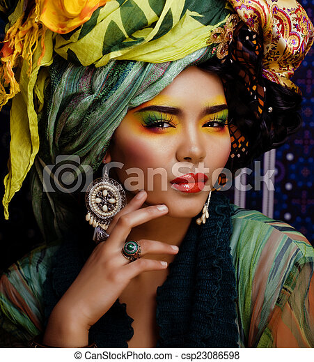 beauty bright woman with creative make up, many shawls on head like cubian, ethno  - csp23086598