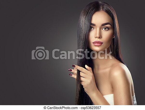 Beauty brunette model girl touching brown long healthy hair - csp53623557