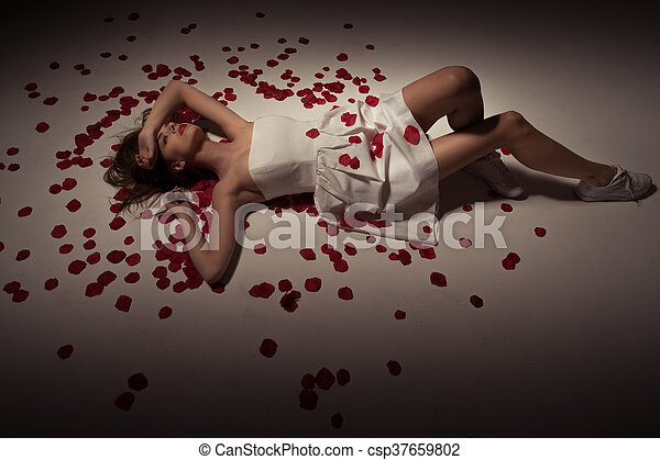 beauty brunette woman wearing white dress and rose petals - csp37659802