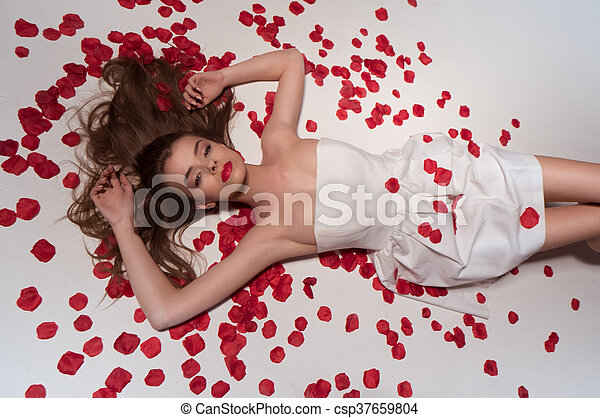 beauty brunette woman wearing white dress and rose petals - csp37659804