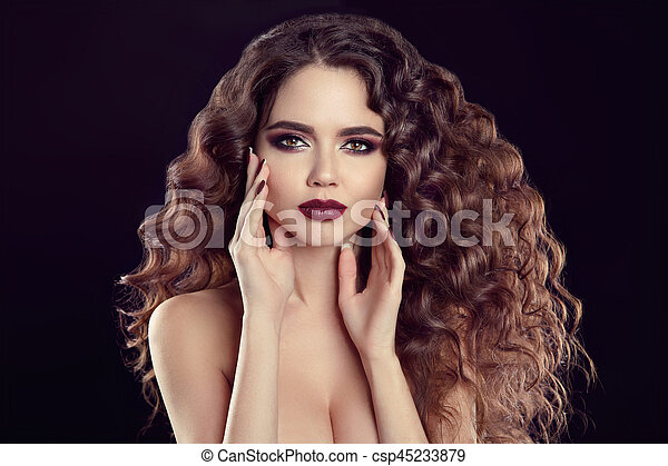 Beauty girl portrait. Beautiful young woman with long curly hair, makeup and manicured nails isolated on black background. - csp45233879