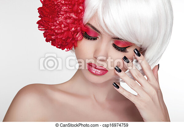 Beauty girl Portrait with red flower. Beautiful Spa Woman Touching her Face. Make up and manicured nails. Perfect Fresh Skin.  - csp16974759