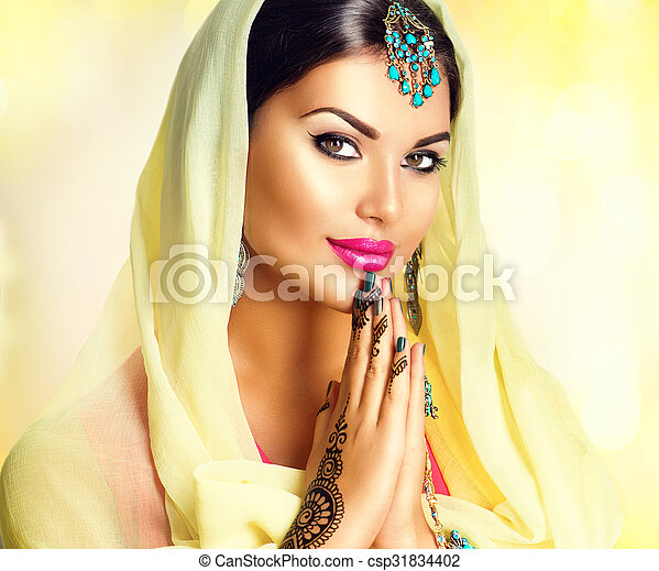 Beauty Indian girl with mehndi tattoos hold palms together - csp31834402