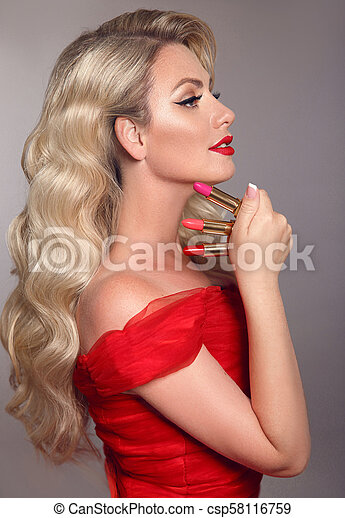 Beauty makeup. fashion glamour portrait of sexy blonde woman with red lips and long wavy hair style holding colourful lipstick over grey studio background. ...