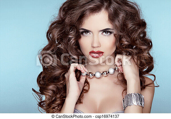 Beauty Portrait. Hairstyle. Fashion brunette girl over blue background. Jewelry accessories. - csp16974137