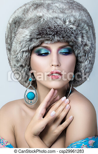 Beauty portrait of young pretty lady wearing fur cap  - csp29961283