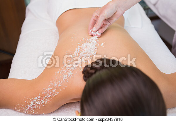 Beauty therapist pouring salt scrub on womans back - csp20437918