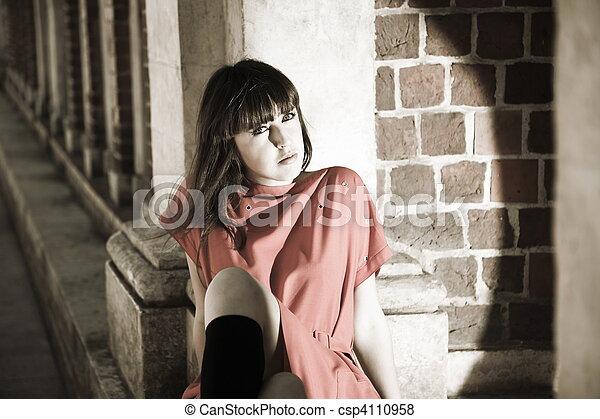 Beauty Woman Sitting Against Brick Border - csp4110958