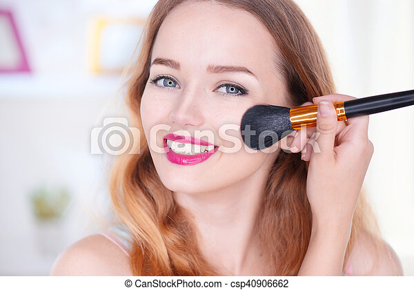 Beauty young woman applying makeup - csp40906662