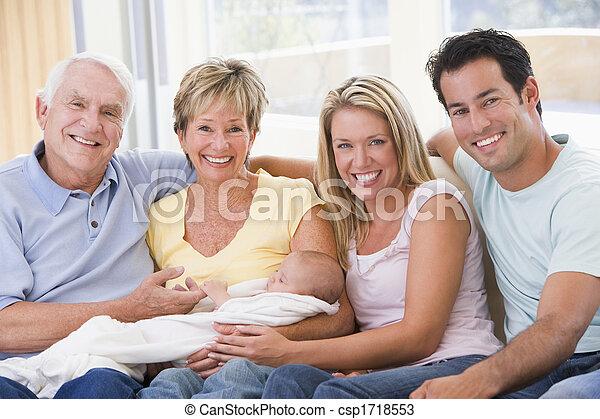 Familia en la sala de estar con bebé sonriendo - csp1718553