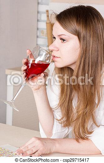Una mujer bebiendo en la cocina - csp29715417