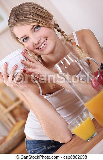Mujer bebiendo en la cocina - csp8862638