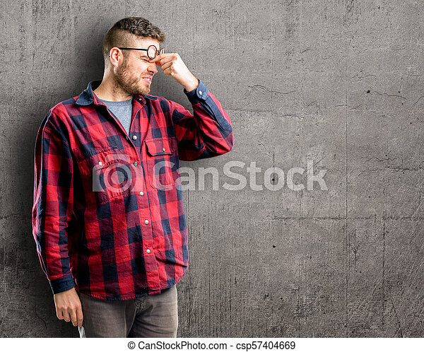 Con expresión somnolienta, con exceso de trabajo y cansancio, se frota la nariz por cansancio - csp57404669