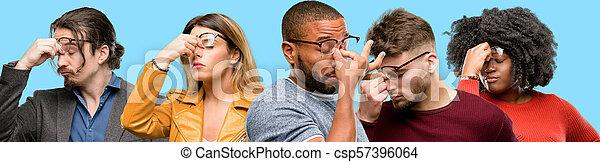 Grupo de personas mezcladas, mujeres y hombres con expresión somnolienta, con exceso de trabajo y cansado, nariz de rubos por cansancio - csp57396064