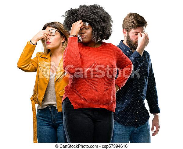 Un grupo de tres hombres y mujeres jóvenes con expresión somnolienta, con exceso de trabajo y cansado, se frota la nariz por cansancio - csp57394616