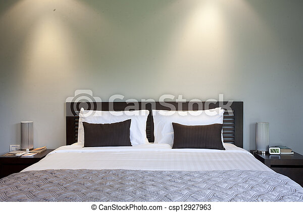 Bed in a hotel room at night - csp12927963