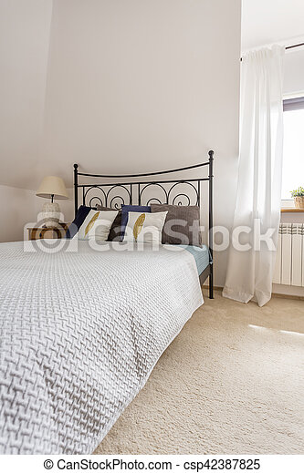 Bed in a white bedroom - csp42387825